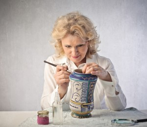Senior woman decorating a ceramic pot